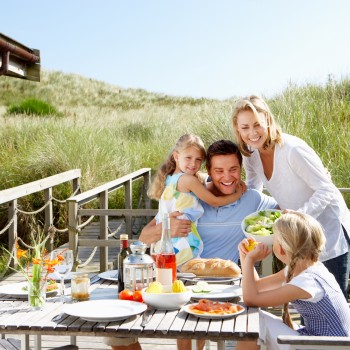Family on vacation eating outdoors near the beach